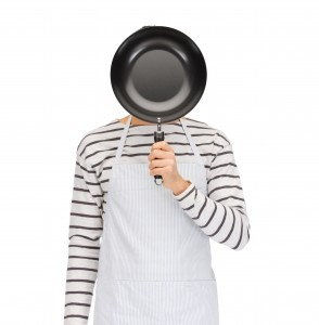 people, cooking, culinary and identity concept - man or cook in apron hiding his face behind frying pan