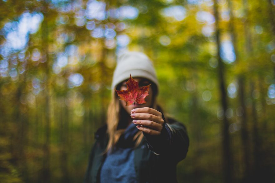 femeie cu o frunza in mana, toamna intr-o padure, femeie cu caciula, astenia de toamna