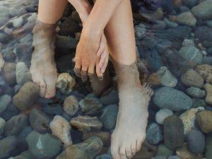 apa termala, femeie care sta cu picioarele in apa, pietre in apa
