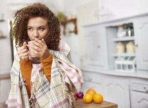 femeie infrigurata, femeie care bea ceai, femeie imbracata gros, femeie cu parul rosu, boli agraveaza frigul
