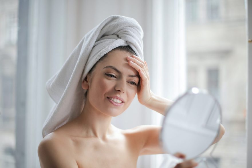 tratamente pentru cicatrici, femeie care s euita in oglinda, femeie cu prosop pe cap