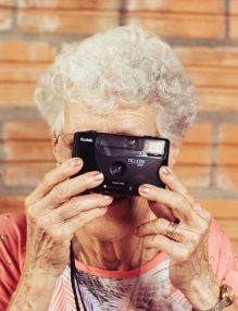 imbatranirea, femeie in varsta vesela care face poze, femeie cu par alb