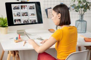 munca de acasa, noul standard munnca la birou, femeie cu bluza galbena care lucreaza la calculator, lucrul de acasa