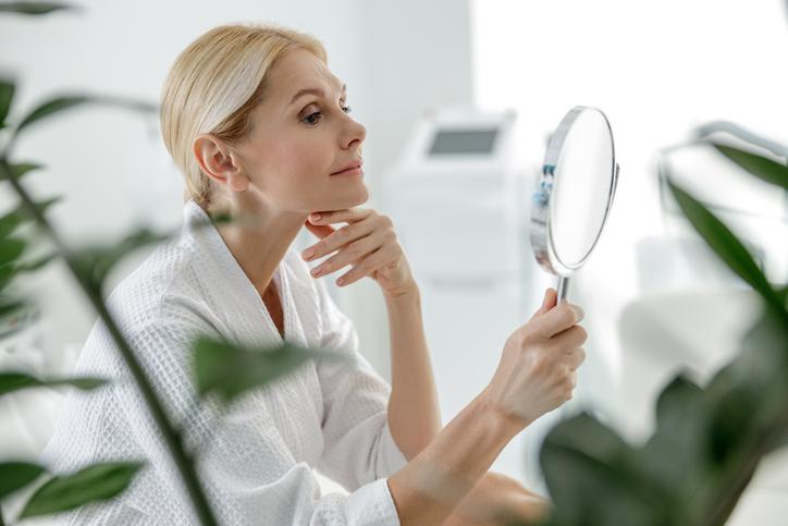 femeie care s euita in oglinda, femeie frumoasa, trucuri ca sa arati mai tanara