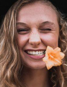 starea de bine, femeie cu floare in gura, femeie frumoasa, femeie vesela